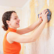 Young woman by rag removes old wallpapers — Stock Photo