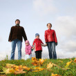 Parents with children stand on meadow at autumn — Stock Photo
