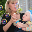 Mother with child is started up with soap bubbles — Stock Photo