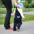 Mother helps child to go — Stock Photo #7444158