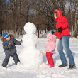 Mother and children make snowman — Stock Photo