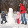 Mother and children make snowman — Stock Photo #7444185