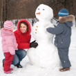 Mother and children make snowman — Stock Photo #7444189