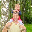Son sits on shoulders at  father — Stock Photo