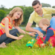 Stock Photo: Child sits on grass with parents and plays with toy