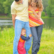Parents on meadow at water and child between legs — Stock Photo
