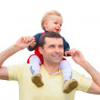 Child sits at father on shoulders — Stock Photo