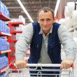 Man in supermarket with shopping cart — Stock Photo