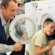 Man looks at washing machine in store, boy glances inward it — Стоковая фотография