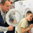Man looks at washing machine in store, boy glances inward it - Stock Photo