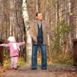 Grandfather with granddaughter on wooden bridge in wood in autumn — Stock Photo