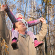Stock Photo: Grandfather with granddaughter on shoulders in wood in autumn