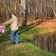 Stock Photo: Grandfather rotates granddaughter in wood in autumn