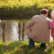 Grandfather with granddaughter in wood in autumn look on ducks in water — Stock Photo