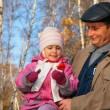Portrait of grandfather with granddaughter in wood in autumn — Stock Photo