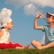 Boy and girl sit on grass and drink from bottle — Stock Photo #7445437