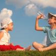 Boy and girl sit on grass and drink from bottle — Stock Photo