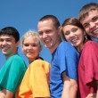 Group of friends in multicolor shirts on sky background — Stock Photo