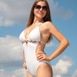 Girl in bathing suit and sunglasses against sky — Stock Photo