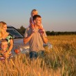 Family with offroad car on wheaten field — Stock Photo #7445871