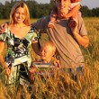 Family on wheaten field — Stock Photo #7445874