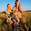 Family on wheaten field — Stock Photo #7445875