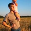 Father hold daughter on shoulder on wheaten field — Stock Photo