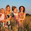 Two mothers with children on wheaten field — Stock Photo #7445898