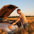 Man at offroad car with lifted cowl on wheaten field — Stock Photo #7445902