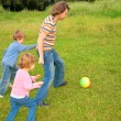 Children play ball with father on grass — Stock Photo