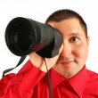 Businessman in red shirt looks in spyglass — Stock Photo #7446513
