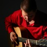 Guitarist in red shirt — Stock Photo