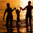 Parents with child in sea on sunset - Stock Photo
