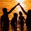 Parents with children in sea on sunset - Stock Photo
