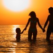 Parents with child in sea on sunset — Stock Photo #7446703