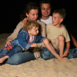 Parents with children sit on sand at night - Stock Photo