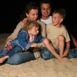 Parents with children sit on sand at night — Stock Photo