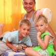 Children with father sitting on bed in room - Foto Stock