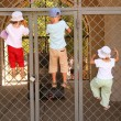 Three children hang on grill of gate - Stock Photo