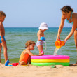 Mother with children to pour water in inflatable pool on shore of sea - Stock Photo