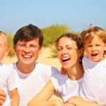 Family portrait on sandy coast — Stock Photo