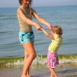 Mother with little girl on beach — Stock Photo