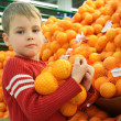Boy with orange in shop — Stock Photo