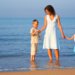 Mother with children standing in water at edge of the sea — Stock Photo #7447004