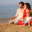 Parents with child sitting on sand on seashore - Stock Photo