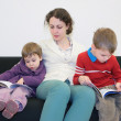 Children with mother read books on sofa — Stock Photo