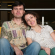 Couple sit on sofa in dark hall - Foto Stock