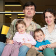 Family sit on sofa in dark hall - Foto Stock