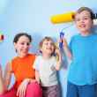 Mother and children with rollers and brushes — Stock Photo