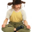 Meditating long-haired Russian man in cap with ear-flaps — Stock Photo #7447282